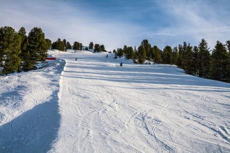 Skiers go down on a ski slope in the Alps. Ski resort in Austria, Zillertal Arena.