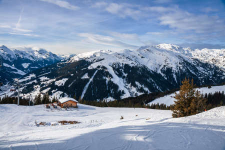 Picturesque alpine winter landscape. Ski slope in the Alps against the backdrop of mountain peaks. Ski resort in Austria, Zillertal Arena. 免版税图像