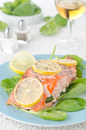 Baked salmon fillet with lemon and spinach closeup photo