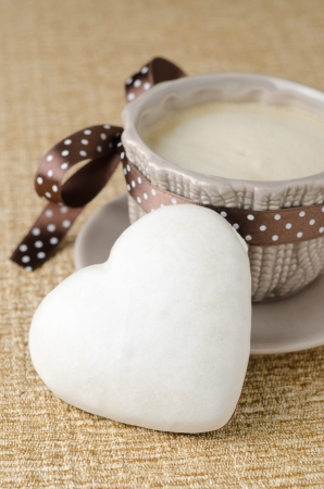 cookie with icing in the form of heart and a cup of coffee, vertical photo