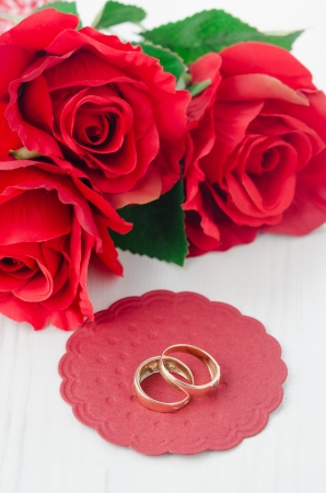 Red roses and rings for Valentine's Day vertical photo