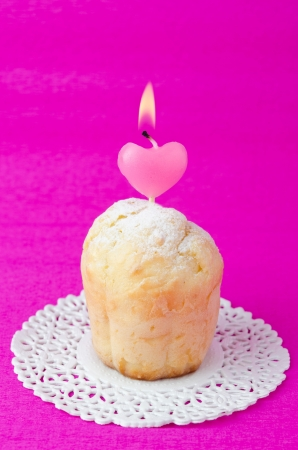 rum baba: Rum Baba decorated with a lighted candle in the form of heart on a pink background