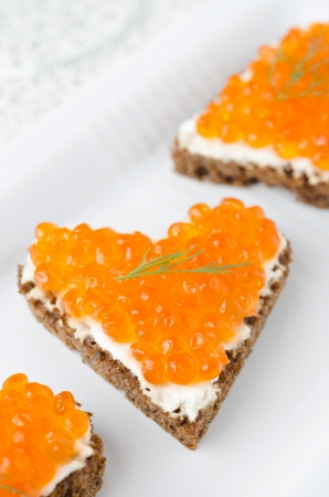 sandwich with red caviar in the form of a heart on white plate photo