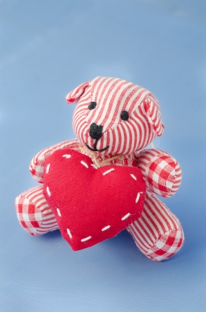 teddy bear with a heart in his hands on a blue background photo