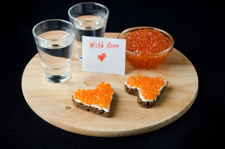 three sandwich with red caviar in the form of a heart, vodka and a card with words of love on a wooden board photo