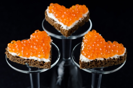 three sandwich with red caviar in the form of a heart on glass stand base photo