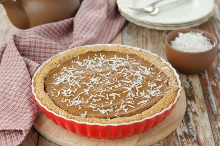 Pie with pumpkin and chocolate in ceramic form on a wooden table photo