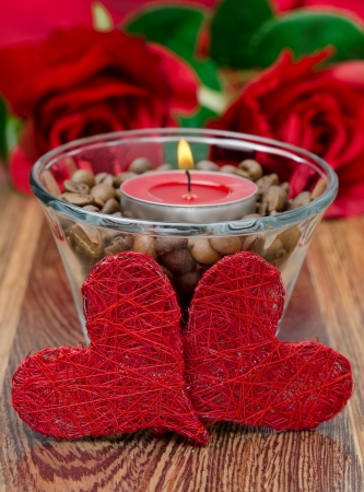 red candle in a glass cup with coffee beans and two hearts for Valentine photo