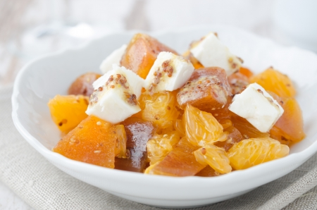salad with persimmon, mandarin oranges and goat cheese with mustard dressing closeup photo