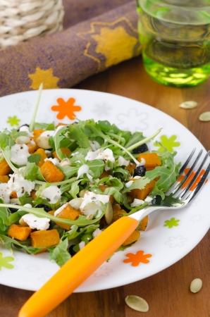 Salad with pumpkin, feta and arugula on a plate photo