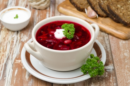 Ukrainian and russian national red borsch with sour cream on the table