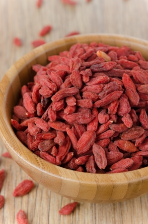 wooden bowl with goji berries on the table closeup photo