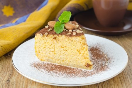 A piece of pumpkin cheesecake, decorated with almonds and a rumpled, sprinkled with cocoa powder on a plate Stock Photo - 17390124