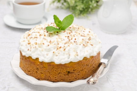 pumpkin cake with cream decorated with nuts and mint
