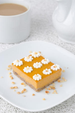 Pumpkin cake, decorated with flowers made of whipped cream and nuts on a plate photo