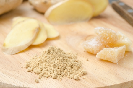three kinds of ginger - dried, fresh and candied on a wooden board closeup photo