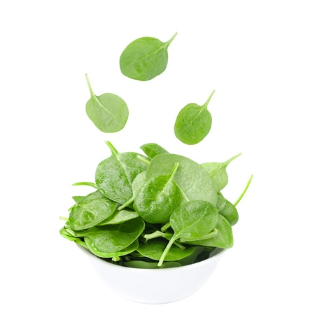 white bowl with fresh spinach and falling leaves isolated on a white background photo