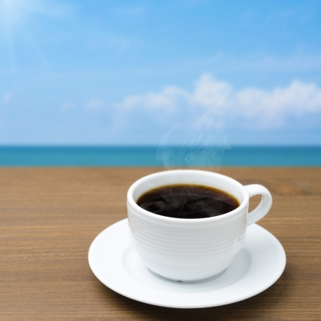 cup of coffee with steam on a wooden table on a background of blue sky photo