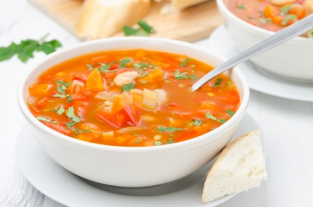 minestrone: Vegetable soup with white beans in a bowl and spoon on a white table horizontal