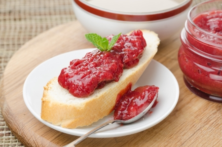 white bread with strawberry jam on a plate photo