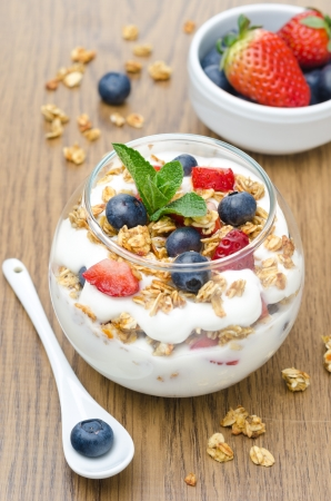 layered dessert with yogurt, granola, fresh berries garnished with mint on a wooden background closeup Foto de archivo