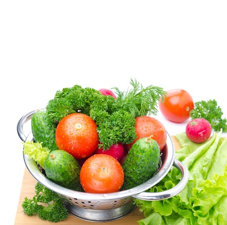 Fresh vegetables and herbs in a metal bowl on a wooden board isolated on a white background photo