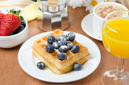 Belgian waffles with blueberries, coffee and orange juice for breakfast  photo