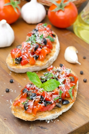 bruschetta with tomato, olives, basil and cheese photo