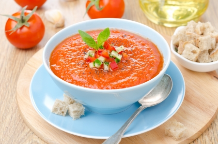 cold tomato soup gazpacho with basil and croutons in a blue bowl, horizontal