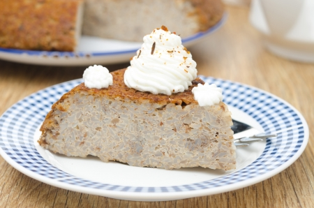 creamer: piece of buckwheat cake  krupenik  with curd cream on a plate horizontal closeup