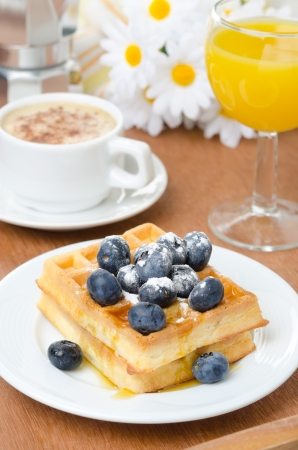 Belgian waffles with blueberries, coffee and orange juice for breakfast vertical photo