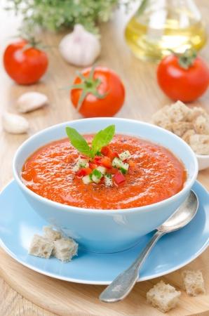 kalte Tomatensuppe Gazpacho mit Basilikum in einer blauen Schale