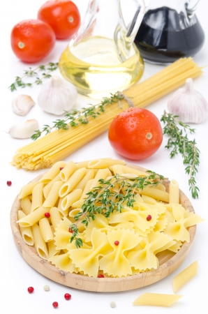 different kinds of Italian pasta, fresh tomatoes, olive oil, balsamic vinegar, thyme, and spices, vertical, isolated on a white background photo