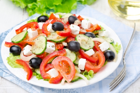 Greek salad with feta cheese, olives and vegetables on a plate, horizontal photo