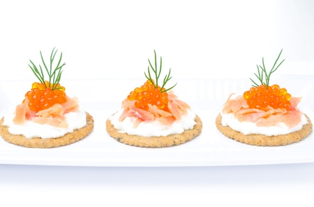 appetizer crackers with cream cheese, salted salmon and red caviar on a white background horizontal photo