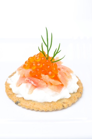 appetizer crackers with cream cheese, salted salmon and red caviar on white background  photo