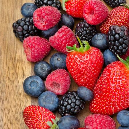 Verschiedene Beeren auf hölzernen Hintergrund Erdbeeren, Himbeeren, Brombeeren, Heidelbeeren Nahaufnahme Draufsicht