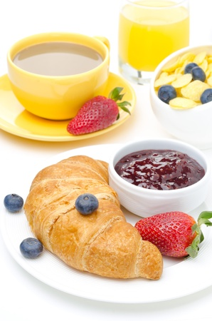 continental breakfast: Breakfast with croissant, jam, fresh berries and coffee with milk on a white background