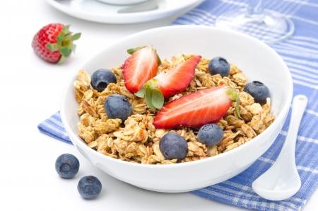 Frühstück mit hausgemachtem Müsli und frischen Beeren auf einem weißen Hintergrund