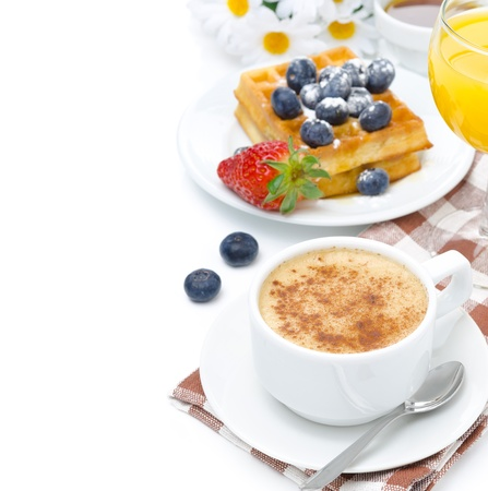 cup of cappuccino, belgian waffles with blueberries and strawberries, orange juice for breakfast isolated on a white background