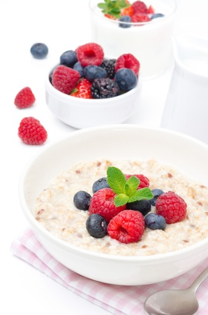 healthy breakfast - oatmeal with fresh berries in a bowl isolated on white, fresh berries and yogurt in the background
