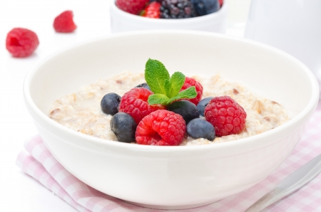 healthy breakfast - oatmeal with fresh berries in a bowl isolated on white, fresh berries in the background, horizontal closeup