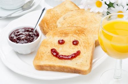 Toast mit einem Lächeln von Marmelade, Kaffee, Orangensaft und frische Orangen zum Frühstück, horizontal closeup