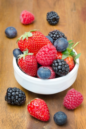 berries in a bowl on a wooden background  strawberries, raspberries, blackberries, blueberries  photo