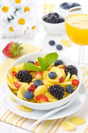 Cornflakes, fresh berries and orange juice for breakfast vertical photo