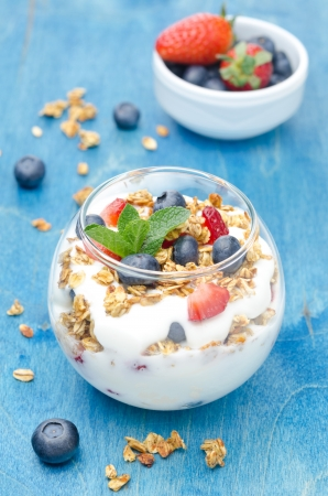 layered dessert with yogurt, granola, fresh berries and a bowl of berries on a blue background vertical photo