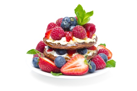 Pancake cake with whipped cream and fresh berries isolated on white background close-up photo