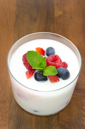 yogurt with different berries and mint in a glass beaker on a wooden background  with strawberries, blueberries, raspberries  top view photo