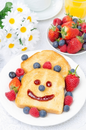 Breakfast with a smiling toast and fresh berries, bowl of berries and flowers in the background, vertical, top view photo