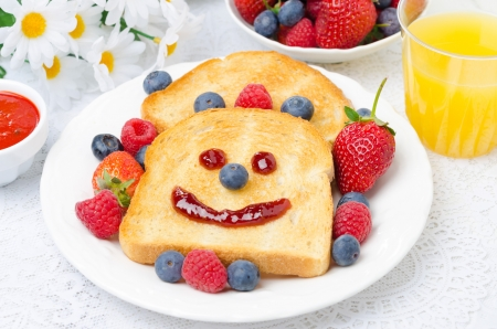 Breakfast with a smiling toast, fresh berries, jam and orange juice, a bowl of berries in the background, horizontal photo